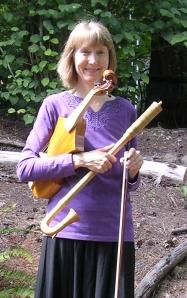 Gayle Neuman holding the viola da braccio (early violin) and tenor krummhorn