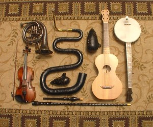 Some of the instruments played by the Oregon Trail Trio.  Top row, left to right: ballad horn, serpent, bass ocarina, guitar, banjo; second row: violin, tenor ocarina; third row: flageolet, fourth row: walking stick recorder