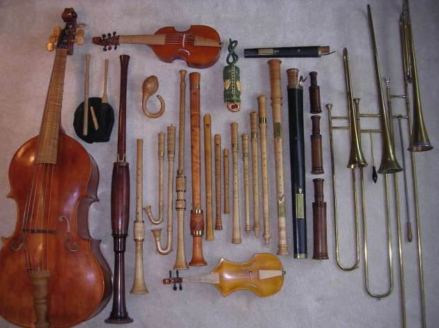 Some of the instruments played by Ensemble De Organographia. Top row, left to right: treble viol, alto curtal; 2nd row: bagpipe, gourd rattle, tartold, tenor alt rackett, tenor sackbutt, bass sackbutt, contrabass sackbutt; 3rd row: violone, tenor shawm, alto shawm, 2 schreierpfeiffen, 2 krummhorns, bass douçaine, 4 recorders, 3 cornamusen, bass Praetorius schreierpfeif, bass rackett, bass curtal; 4th row: great bass rackett; 5th row: viola da braccio, spinettino